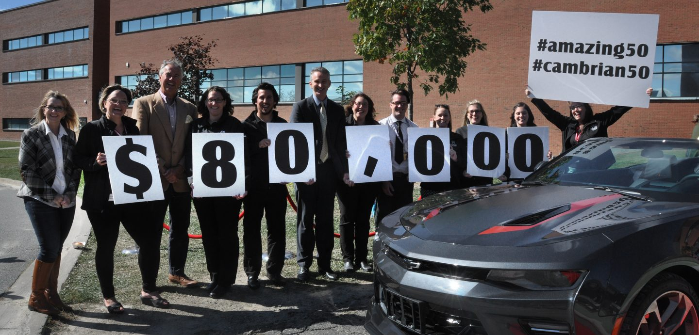 People hold signs showing that Cambrian College's 50th-anniversary Camaro raffle raised $80,000 for student scholarships and bursaries. The winner was declared on September 28.