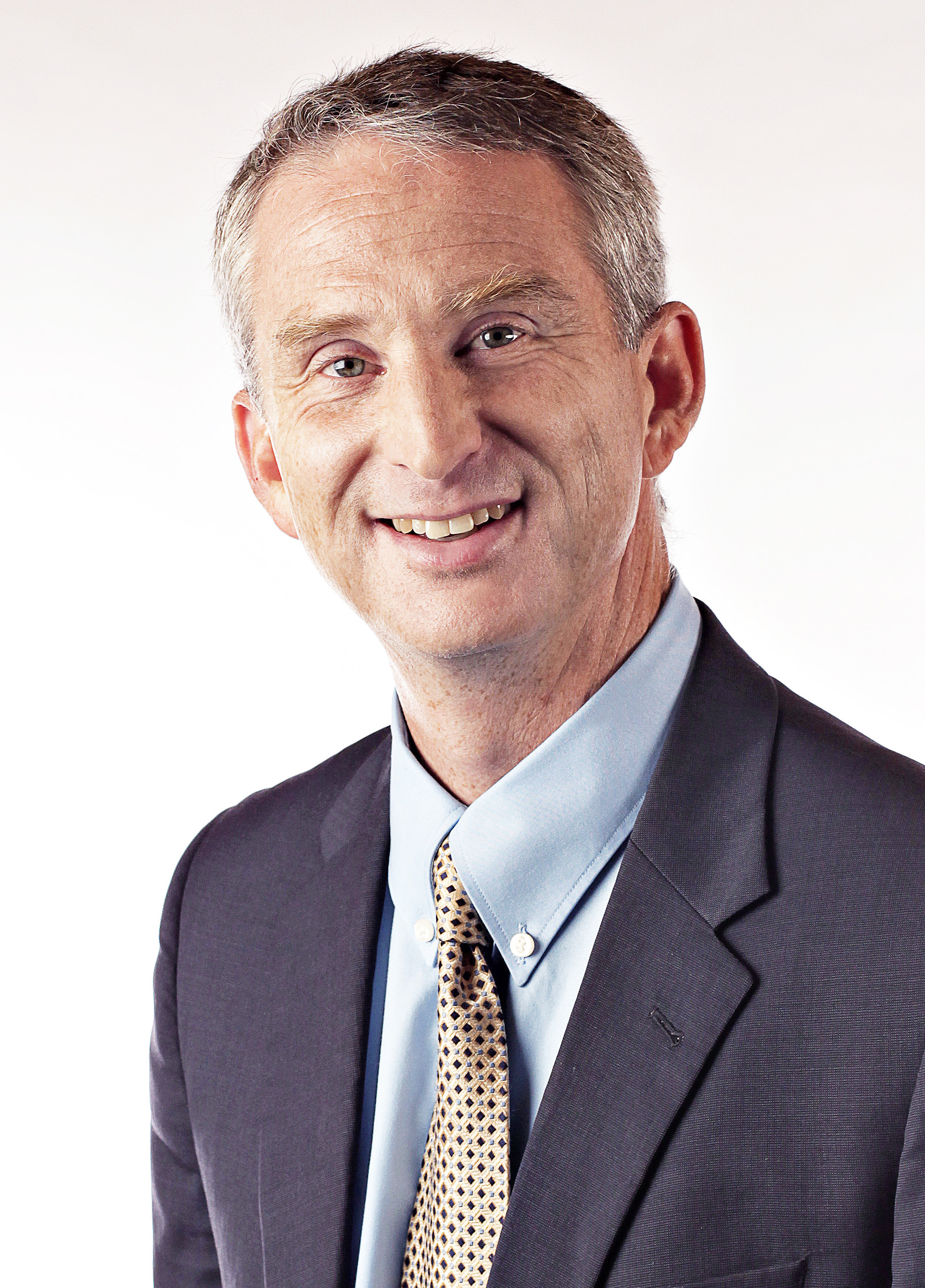 Image Description: In the photo is Cambrian College President Bill Best posing and smiling, he is wearing a dark blue suit and a light blue shirt. The background is completely white.